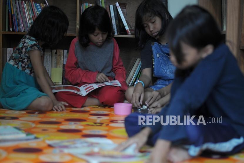 Anak-anak membaca buku di Taman Baca Bulian, Jagakarsa, Jakarta, Senin (12/3).