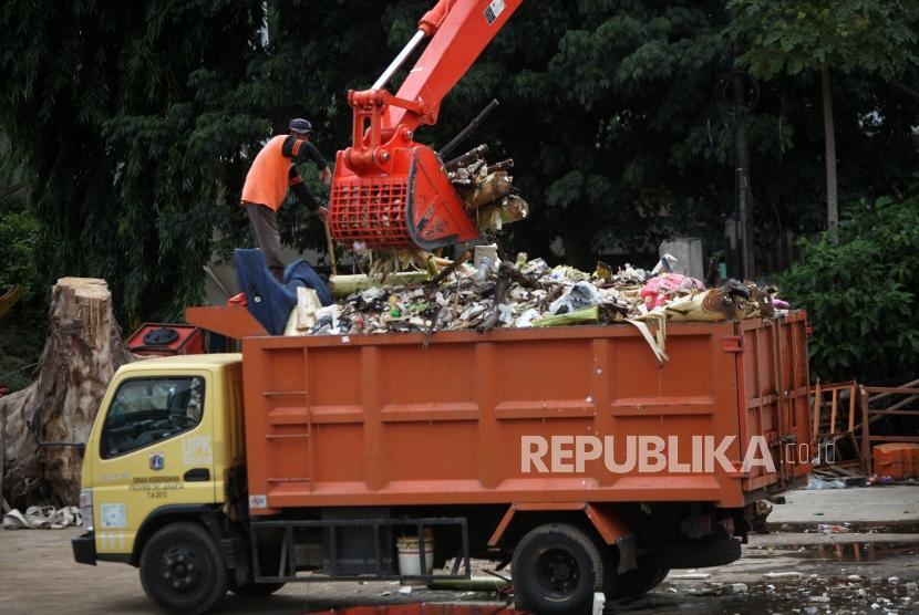 Petugas menggunakan alat berat mengangkut sampah di Pintu Air Manggarai, Jakarta, Rabu (13/12).