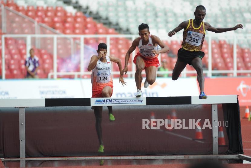 Pelari putra Sri Lanka R.M.S. Pushpalrumara (kanan) melintasi rintangan diikuti dua pelari Indonesia Atjong Tio Purwanto (tengah) dan Elizar Gamashi pada lari halang rintang 3000m putra 18th Asian Games Invitation Tournament di Stadion Utama Gelora Bung Karno Senayan, Jakarta, Rabu (14/2).