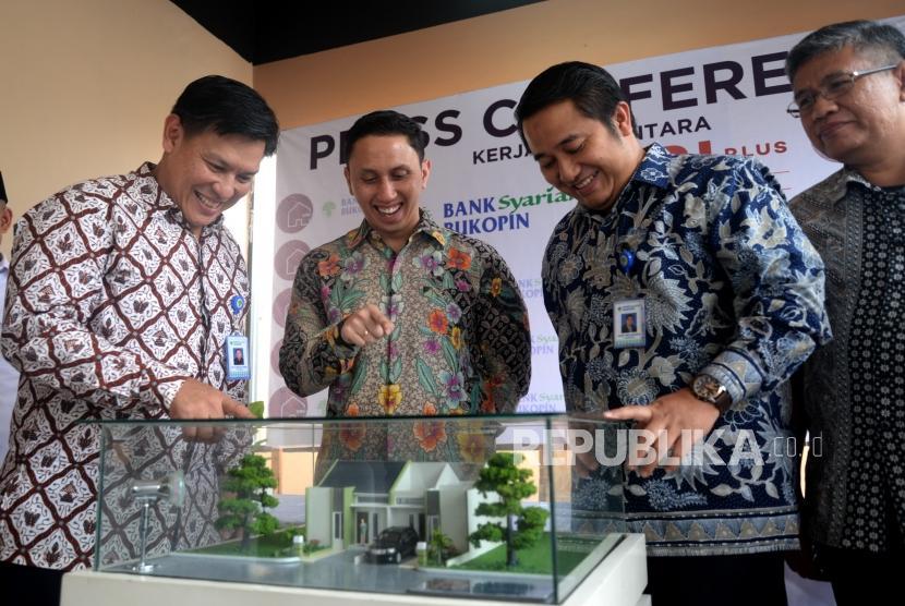 Kepala Divisi Pembiayaan Komersial PT. Bank Syariah Bukopin (BSB) Okto Abriano Kesur, Direktur Utama PT. Asfi Ilhami Rayhan (PT.AIR) Keisar Rachmat Magfirat, dan Kepala Divisi Bisnis Area V Capem BSD BSB Dony Wicaksono (dari kiri) melihat maket perumahan Villa Rizky Islami Plus usai konfrensi pers kerjasama pembiayaan di Tangerang, Banten, Selasa (9/1) .