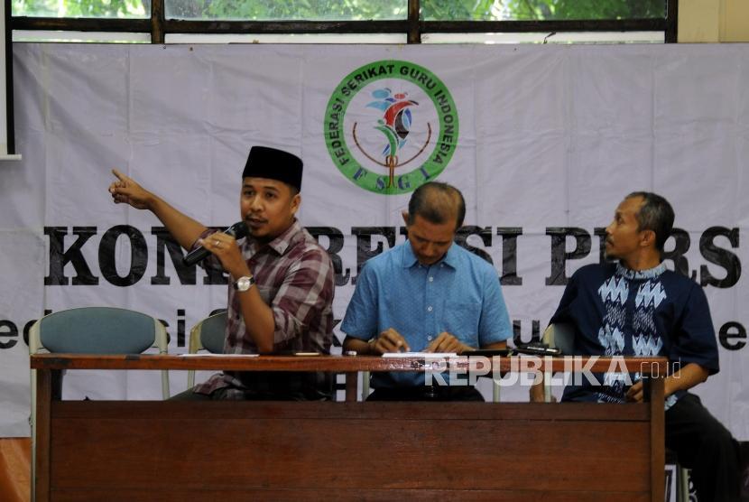Sekjen Federasi Serikat Guru Indonesia (FSGI) Heru Purnomo (tengah) didampingi Wakil Sekjen FSGI Satriwan Salim (kiri) dan Bendahara FSGI Slamet Maryanto (kanan) memberikan penjelasan saat konferensi pers di Gedung LBH Jakarta, Ahad (3/12).