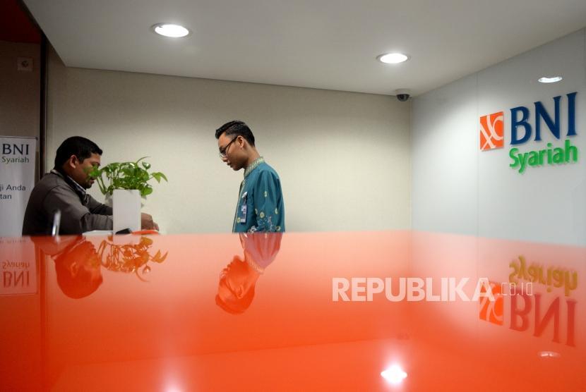 Petugas melayani transaksi nasabah di kantor layanan BNI Syariah, Jakarta. ilustrasi