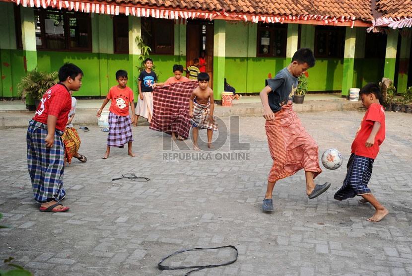Warga mengikuti lomba pertandingan bola mengunakan sarung saat perayaan HUT ke-69 RI di Margahayu, Bekasi, Jawa Barat, Ahad (17/8). (Republika/Tahta Aidilla)