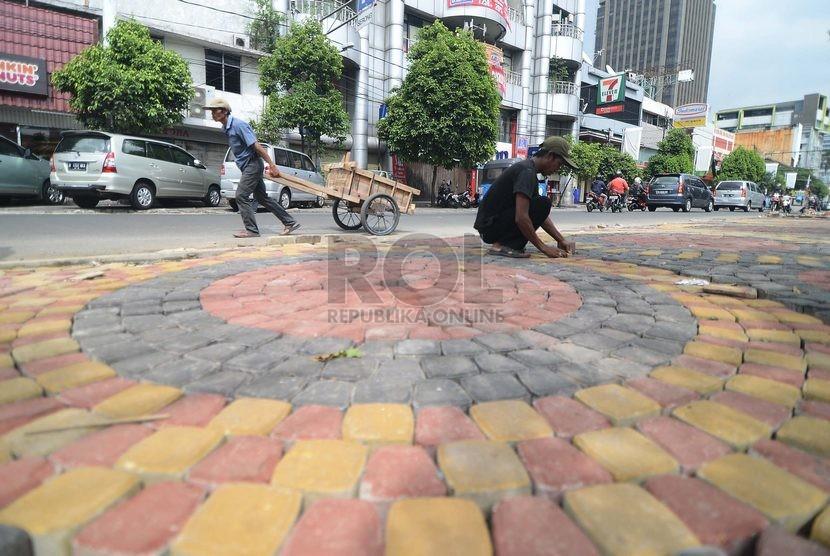 Pekerja menata batu paving blok (ilustrasi)