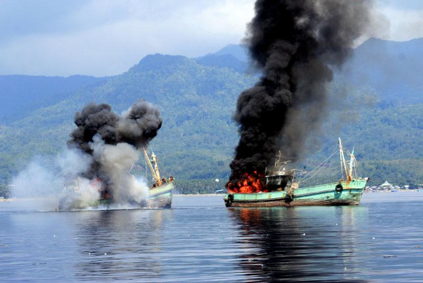 Dua kapal ikan ilegal berbendera Papua Nugini meledak dan mengeluarkan api ketika ditenggelamkan personel Lantamal IX Ambon di Perairan Teluk Ambon, Maluku, Ahad (21/12). (Antara/Izaac Mulyawan)
