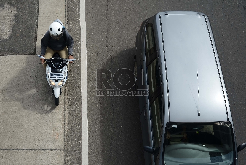 Sejumlah pengendara sepeda motor melintas di Jalan Sudirman, Jakarta Selatan, Selasa (6/1).  (Republika/Raisan Al Farisi)
