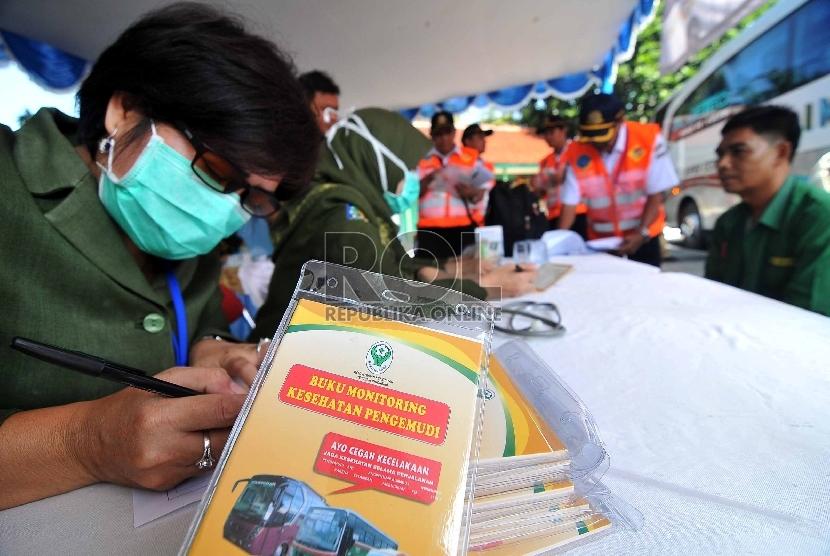 Petugas melakukan pemeriksaan kesehatan terhadap seorang supir Bus AKAP saat melakukan inspeksi keselamatan lalulintas di terminal Kampung Rambutan, Jakarta, Senin (23/3).   (Republika/Rakhmawaty La'lang)