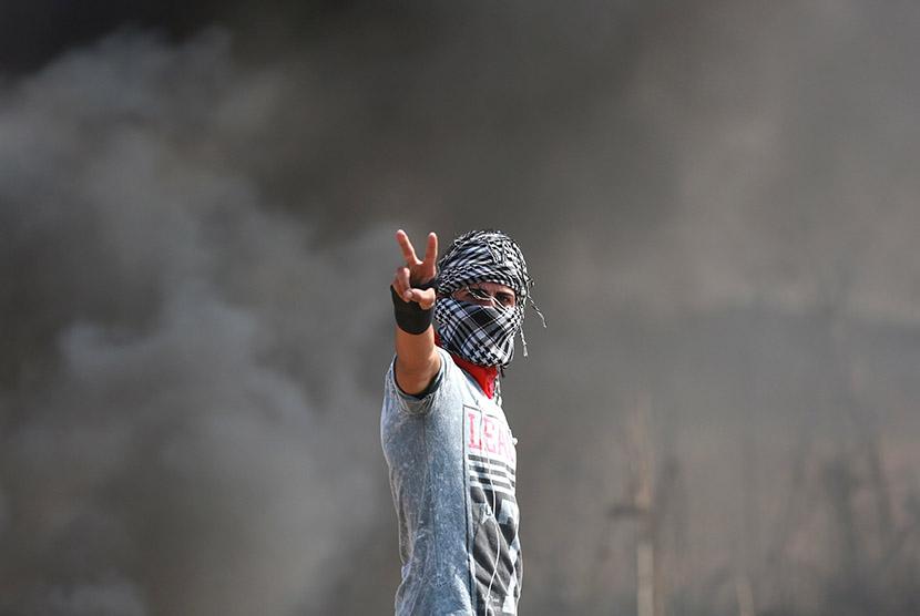 Ekspresi pemuda Palestina saat terlibat bentrok dengan pasukan pendudukan Israel di dekat perbatasan Gaza dengan Israel, Sabtu (10/10). (REUTERS/Yasser Gdeeh)