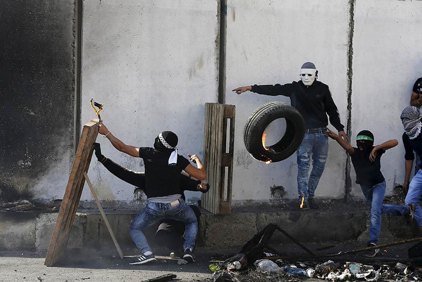 Pengunjuk rasa Palestina bentrok dengan pasukan pendudukan Israel di dekat kamp pengungsian Shuafat, Yerusalem, Palestina.   (REUTERS/Ammar Awad)