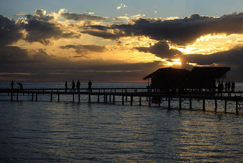 Wisatawan berjalan di jembatan sekitar hotel yang dibangun di pulau Cinta, Boalemo, Gorontalo, Sabtu (30/1).   (Antara/Wahyu Putro)