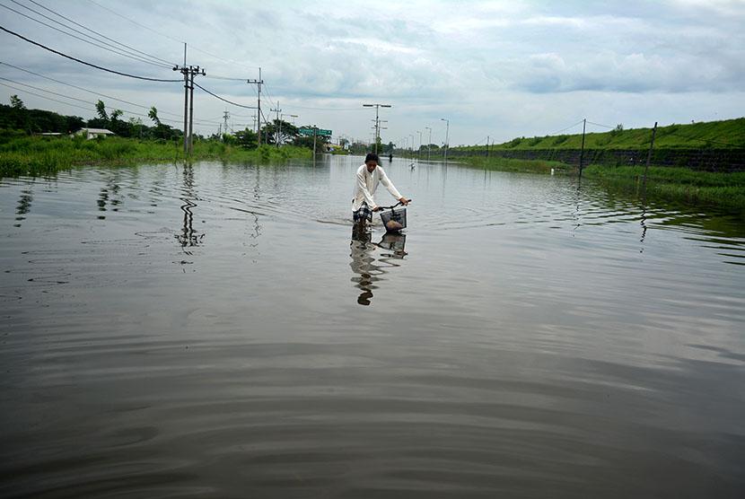 Seorang anak melintasi banjir di jalan raya Porong, Sidoarjo, Jawa Timur, Jumat (12/2).  (Antara/Umarul Faruq)