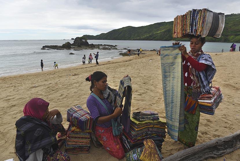 Para pedagang souvenir menjajakan dagangannya berupa kain khas Suku Sasak kepada wisatawan di pantai Kuta, Lombok, Nusa Tenggara Barat, Jumat (20/1).