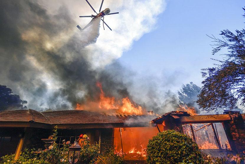 Sebuah helikopter berupaya memadakan api akibat kebakaran hutan dahsyat yang melanda Kalifornia, Senin (9/10).