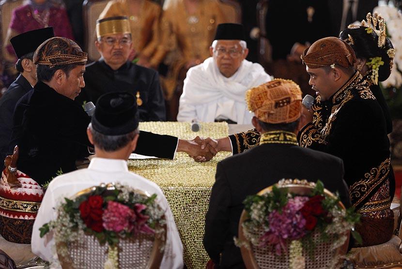 Presiden Joko Widodo (kiri) menikahkan putrinya, Kahiyang Ayu (kanan) dengan Bobby Nasution (kedua kanan) disaksikan Wakil Presiden Jusuf Kalla (kedua kiri) dan Ketua MUI KH Ma'ruf Amin (keempat kanan) saat ijab kabul di Gedung Graha Saba, Sumber, Solo, Jawa Tengah, Rabu (8/11).