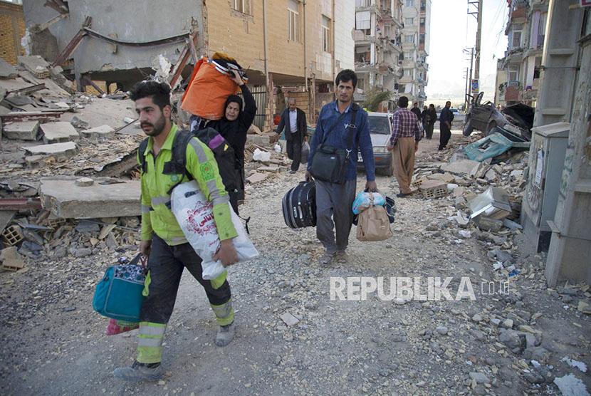 Warga mengevakuasi barang-barang milik mereka dari reruntuhan bangunan yang hancur akibat gempa di kota Sarpol-e-Zahab di Provinsi Kermanshah, Iran, Senin (13/11).