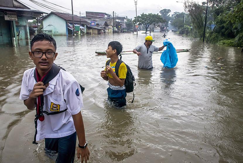 Warga melintasi banjir di kawasan Baleendah, Kabupaten Bandung, Jawa Barat, Senin (13/11).