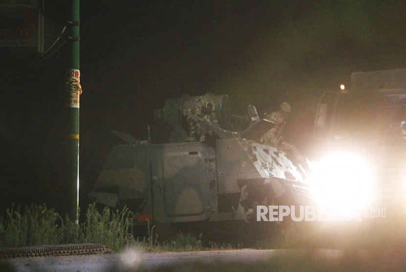 Tentara bersenjata Zimbabwe duduk di atas tank di Harare, Zimbabwe, Rabu dini hari (15/11).