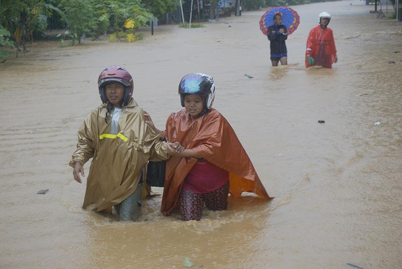 Warga menyeberangi banjir bandang yang memutus jalur lintas selatan Desa Hadiwarno, Pacitan, Jawa Timur, Selasa (28/11).