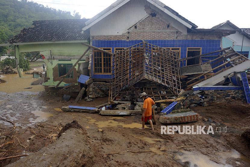 Warga memeriksa rumahnya yang porak-poranda diterjang banjir bandang di Pacitan, Jawa Timur, Rabu (29/11).
