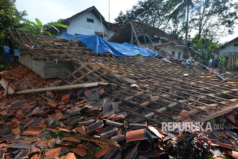 Warga menyaksikan rumah permanen berlantai dua yang ambruk akibat gempa bumi di Desa Gunung Sari, Jawa Barat, Sabtu (16/12).