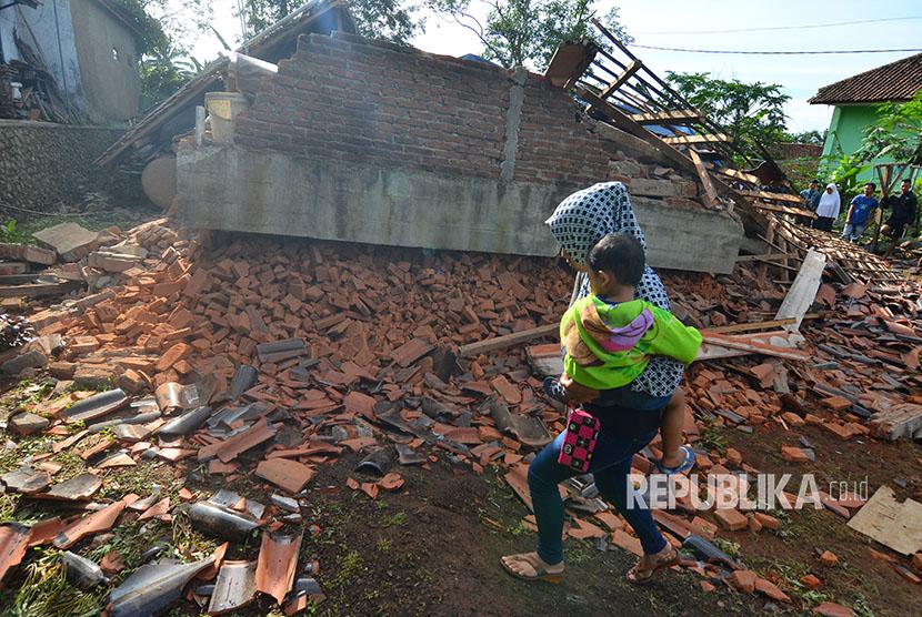 Warrga melintas di depan rumah permanen berlantai dua yang ambruk akibat gempa bumi di Desa Gunung Sari, Jawa Barat, Sabtu (16/12).
