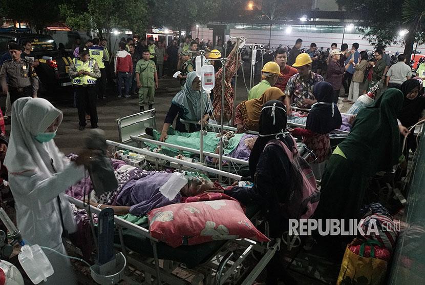 Sejumlah petugas melakukan penanganan medis terhadap pasien yang dievakuasi di pelataran parkir, akibat gempa 6,9 SR, di RSUD Banyumas, Jateng, Sabtu (16/12).