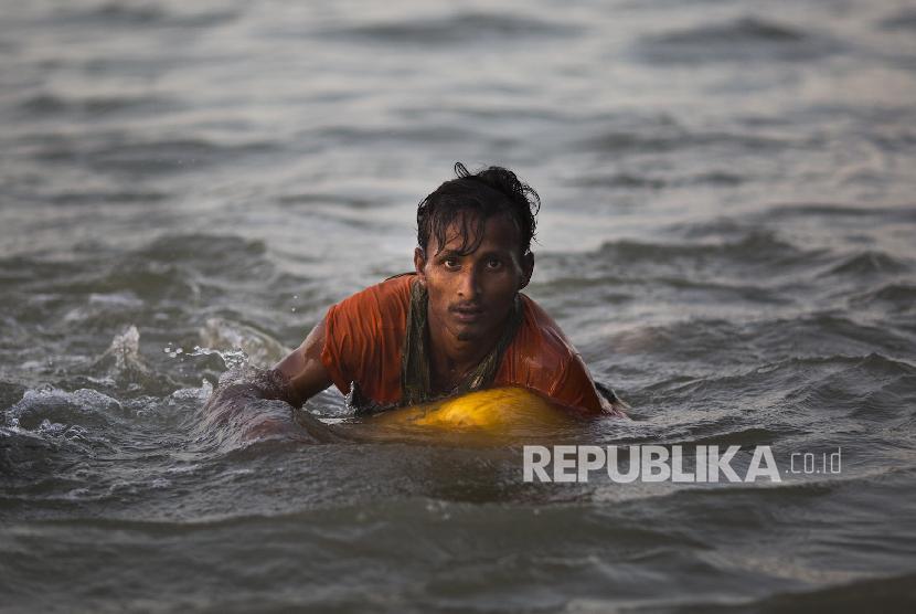 Seorang pria Rohingya berusaha melewati sungai Naf di perbatasan Myanmar-Bangladesh, untuk melarikan diri dari genosida militer Myanmar terhadap muslim Rohingya.