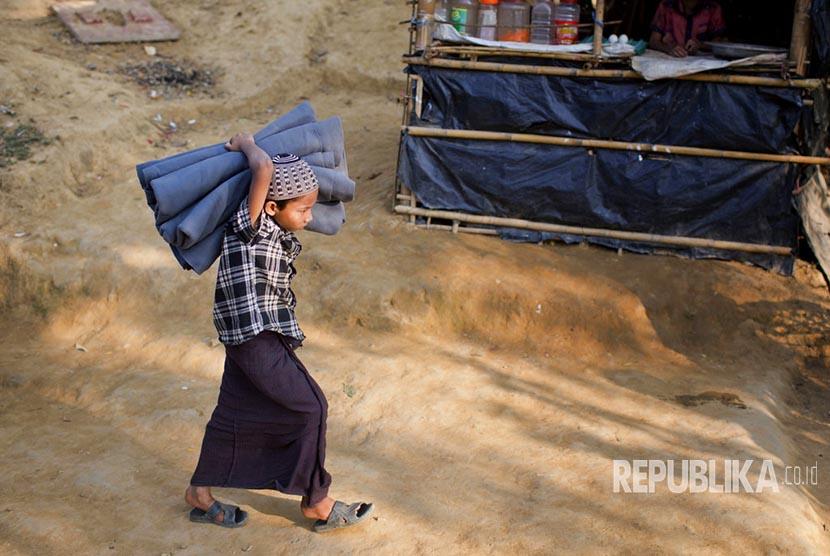 Seorang anak pengungsi Muslim Rohingya membawa selimut di lokasi pengungsian Kutupalong di Ukhiya, Bangladesh, Kamis (21/12).