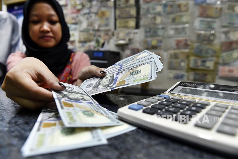 Petugas jasa penukaran uang asing menghitung pecahan 100 dolar AS di ITC Kuningan, Jakarta, Rabu (28/2).