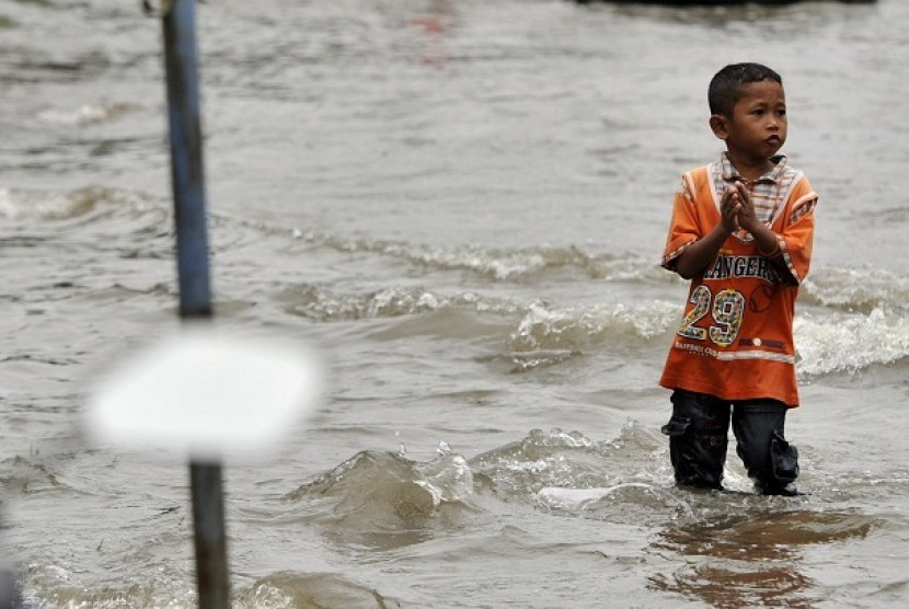 A boy walks in an inundated street. (illustration)