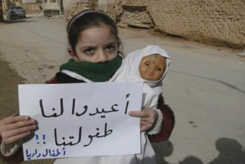 A girl holds a doll and a banner during a protest against Syria's President Bashar al-Assad in Daria, near Damascus, February 12, 2012. The banner reads: Bring back our childhood.