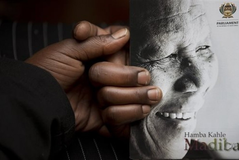 A man holds the official programme ahead of the memorial service for former South African president Nelson Mandela at the FNB Stadium in the Johannesburg, South Africa township of Soweto, Tuesday, Dec. 10, 2013.
