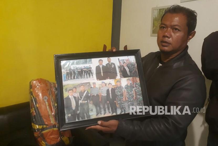 Adik ipar almarhum Ustaz Prawoto, Haji Didin tengah memperlihatkan foto-foto almarhum di kediamannya di Cigondewah Kidul, Kota Bandung, Jumat (2/2).