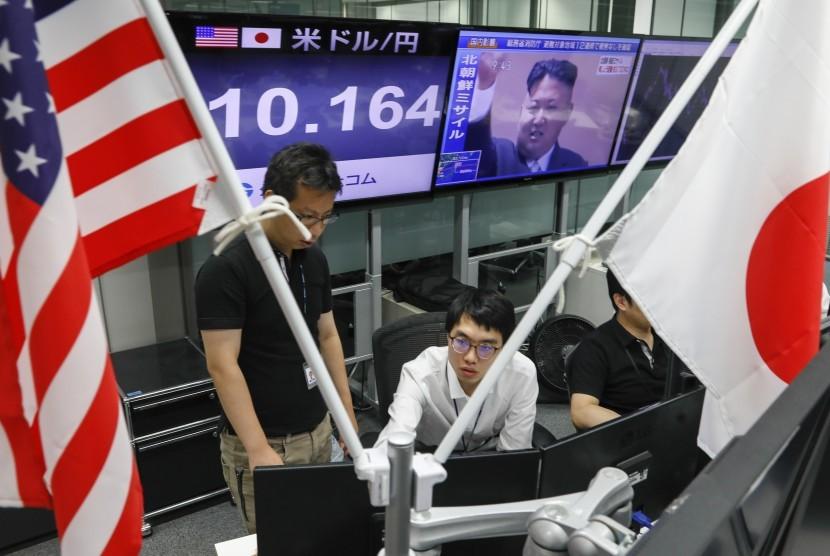 Aktivitas di pasar saham saat sesi perdagangan pagi ketika televisi menayangkan pemimpin Korea Utara Kim Jong-un, di Tokyo, Jepang, Jumat (15/9). Korea Utara meluncurkan rudal balistik atas Jepang yang dilaporkan jatuh di Samudera Pasifik, sekitar 2.000 km di timur Hokkaido, pulau yang terletak di bagian utara Jepang Hokkaido.