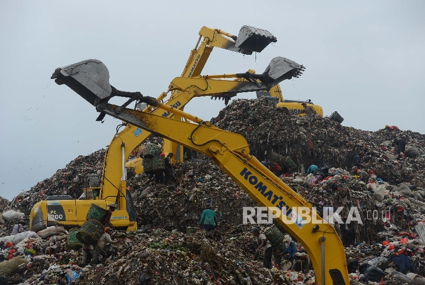 Aktivitas pemulung bersama alat berat di Tempat Pengolahan Sampah Terpadu (TPST) Bantar Gebang, Bekasi, Jawa Barat, Kamis (11/2).  (Republika/Raisan Al Farisi)