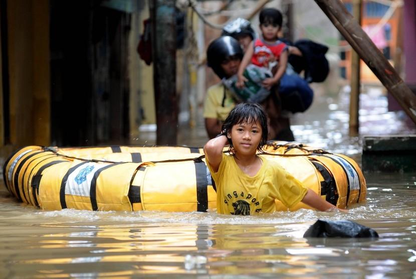 Aktivitas warga saat banjir masih merendam ratusan rumah mereka di kawasan Kampung Melayu, Kampung Pulo, Jakarta Timur, Rabu (4/4). (Republika/Prayogi)