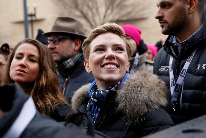 Aktris Scarlett Johansson tersenyum saat berdemonstrasi memprotes Presiden Amerika Serikat Donald Trump, di Washington, Sabtu (21/1).