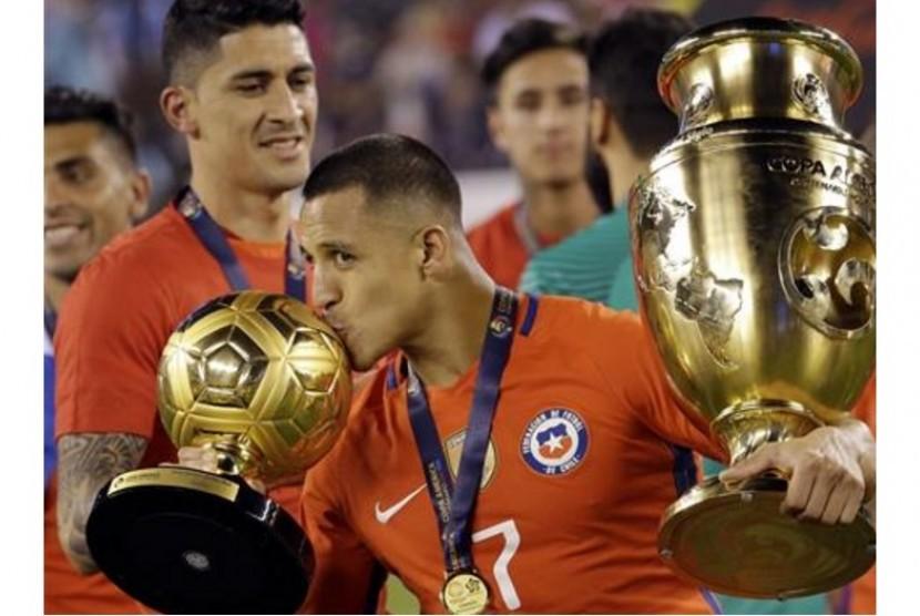 Alexis Sanchez mencium trofi pemain terbaik Copa America Centenario 2016.