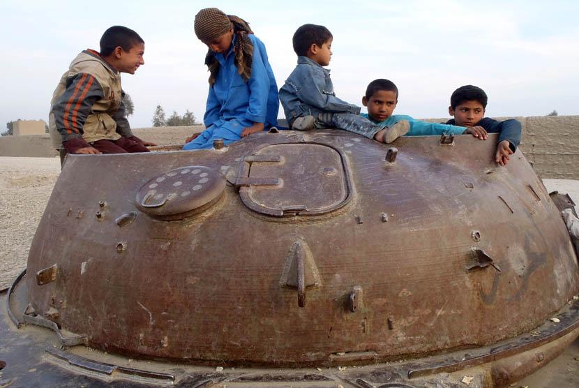 Anak-anak afghanistan bermain di bangkai tank soviet di distrik