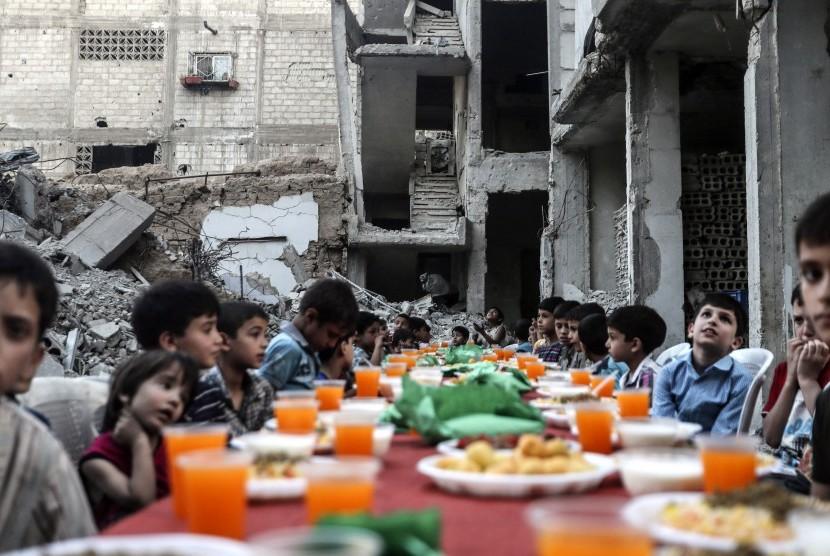 Anak-anak duduk menunggu iftar atau buka puasa di samping puing-puing dan reruntuhan bangunan, di Douma, Suriah, 17 Juni 2017.