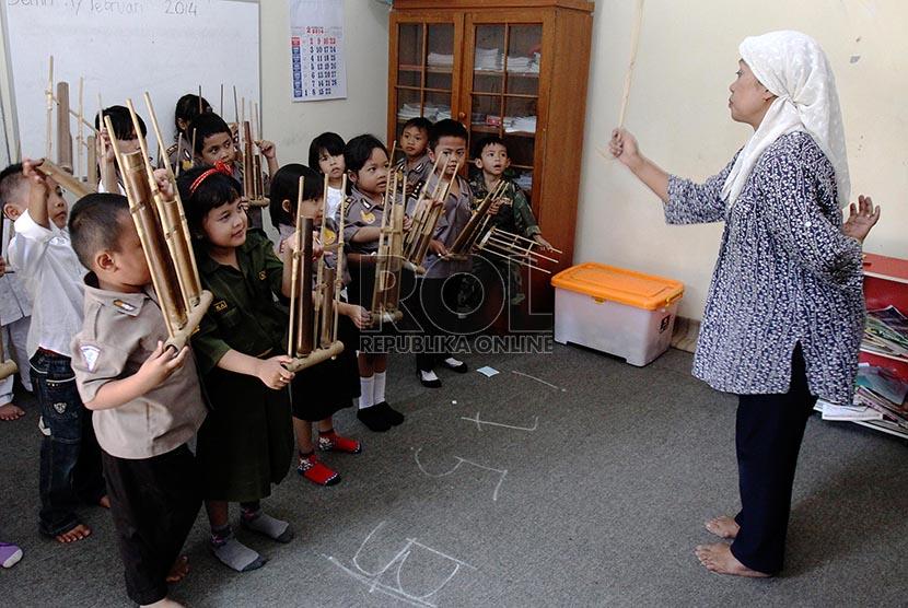 Anak-anak kelas B PAUD Mekar Gondangdia belajar bermain alat musik angklung, Jakarta Pusat, Kamis (20/2).