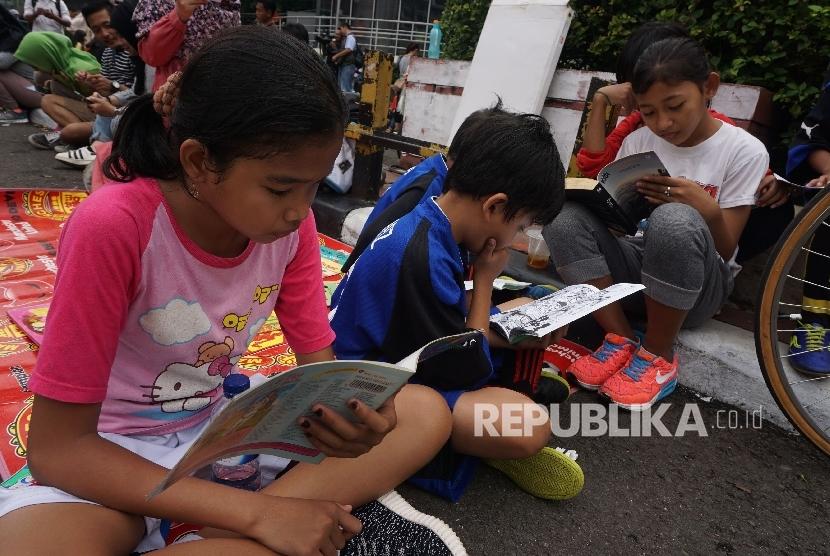 Anak-anak membaca buku di stand komunitas Buku 100 Desa saat berlansungya Car Free Day di Bundaran HI, Jakarta, Ahad (2/4).