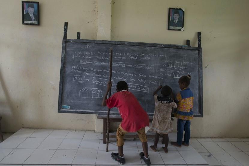 Anak-anak mencoba menulis di papan tulis di salah satu sekolah dasar di Kabupaten Maybrat, Papua Barat, Kamis (21/4). (Antara/Rosa Panggabean)