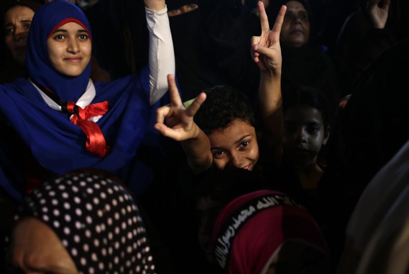 Anak-anak Mesir mengacungkan jari tanda kemenangan saat bergabung dengan aksi unjuk rasa menolak kudeta dan mendukung Presiden Mursi di luar Masjid Rabiah Al Adawiyah, Nasr City, Kairo, Rabu (31/7).   (AP / Khalil Hamra)