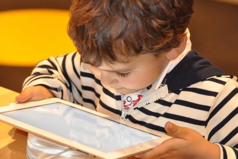 Anak bermain tablet layar sentuh.