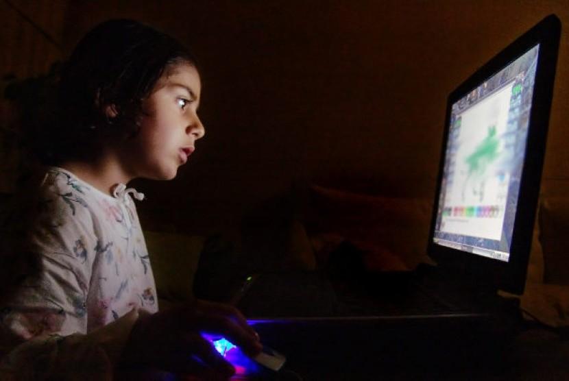 Anak dengan komputer. Orangtua harus mengawasi anak dalam penggunaan teknologi dan layanan di internet untuk menghindarkan mereka dari pornografi.