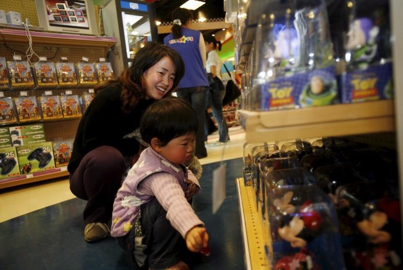 Anak di toko mainan bersama ibunya.