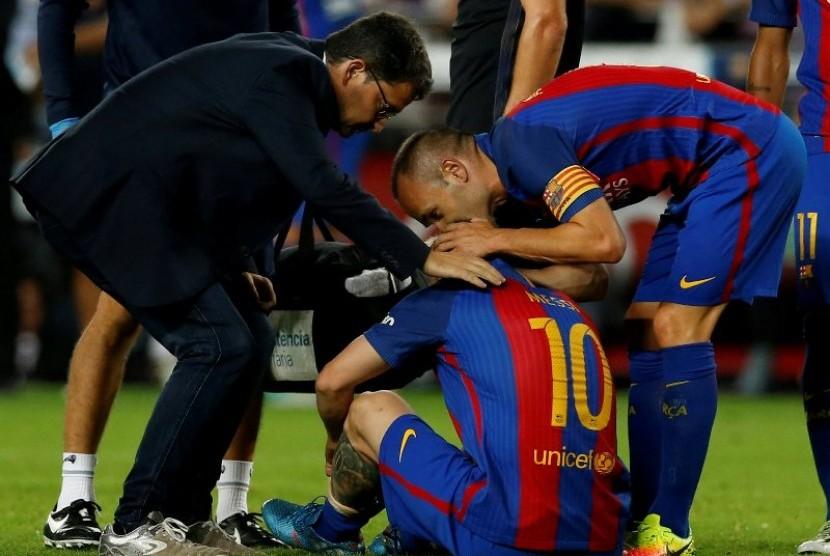 Andres Iniesta (kanan) menghibur Lionel Messi yang cedera.