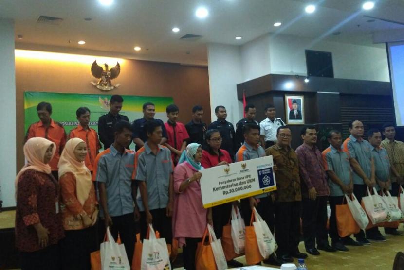 Anggota Badan Amil Zakat Nasional (BAZNAS) melakukan sosialisasi zakat dan penyerahan secara simbolis penyaluran dana zakat ASN Kemenkop untuk mustahik di Kantor Kemenkop, Jakarta, Jumat (23/2).