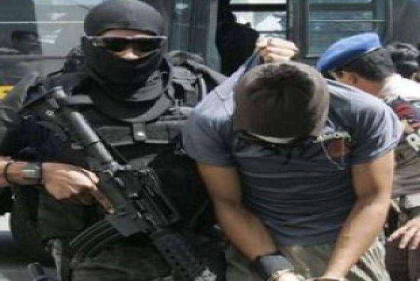 Anggota Densus 88 sedang menggiring teroris yang tertangkap
